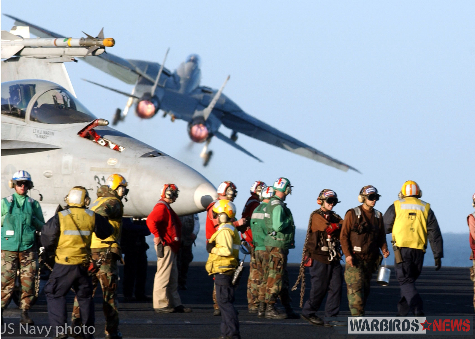 "At sea aboard USS Theodore Roosevelt (CVN 71) Jan. 17, 2002 - Squadron and ships company personnel conduct maintenance and equipment checks on the flight deck, while and F-14 ""Tomcat"" assigned to the ""Diamondbacks"" of Fighter Squadron One Zero Two (VF-102) launches from one of two steam catapults located on the ships bow. Theodore Roosevelt and her embarked Carrier Air Wing One (CVW-1) are conducting missions in support of Operation Enduring Freedom. U.S. Navy Photo by Photographer's Mate 3rd Class Stacey Hines (RELEASED)"