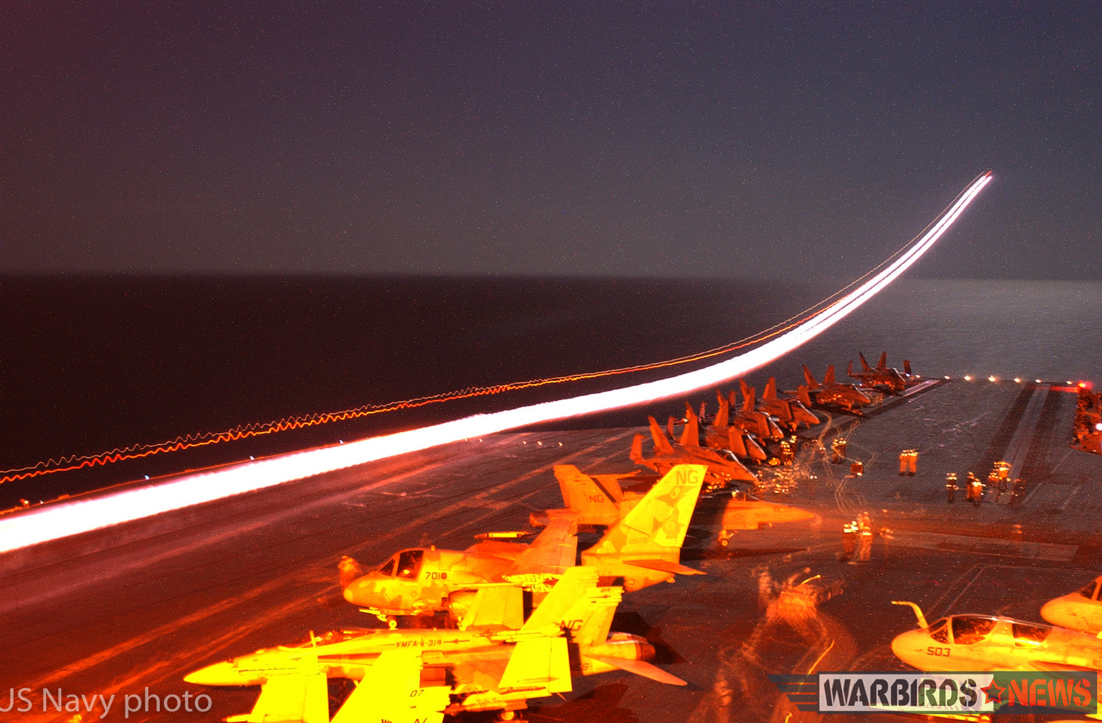 """At sea aboard USS John C. Stennis (CVN 74) Mar. 1, 2002 - A timed photographic exposure of an F-14A """"Tomcat"""" launching from the flight deck displays the afterburner trail of the aircraft as it accelerates away from the ship. John C. Stennis and Carrier Air Wing Nine (CVW-9) are conducting combat missions in support of Operation Enduring Freedom. U.S. Navy photo by Photographer's Mate Airman Michael Arteaga. (RELEASED)"""