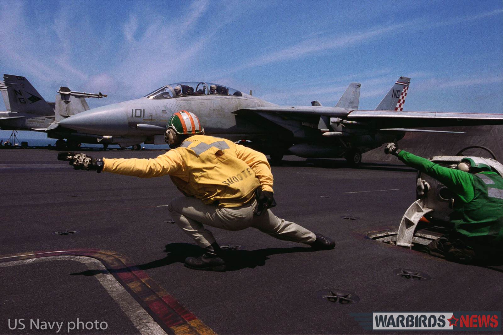 "At sea aboard USS John C. Stennis (CVN 74) Apr. 12, 2002 -- Lt. David Sanderson from San Diego, CA, gives the launch signal to the pilot of an F-14 ""Tomcat"" assigned to the ""Checkmates"" of Fighter Squadron Two One One (VF-211). John C. Stennis and Carrier Air Wing Nine (CVW-9) are conducting combat missions in support of Operation Enduring Freedom. U.S. Navy photo by Photographer's Mate 3rd Class Jayme T. Pastoric. (RELEASED)"