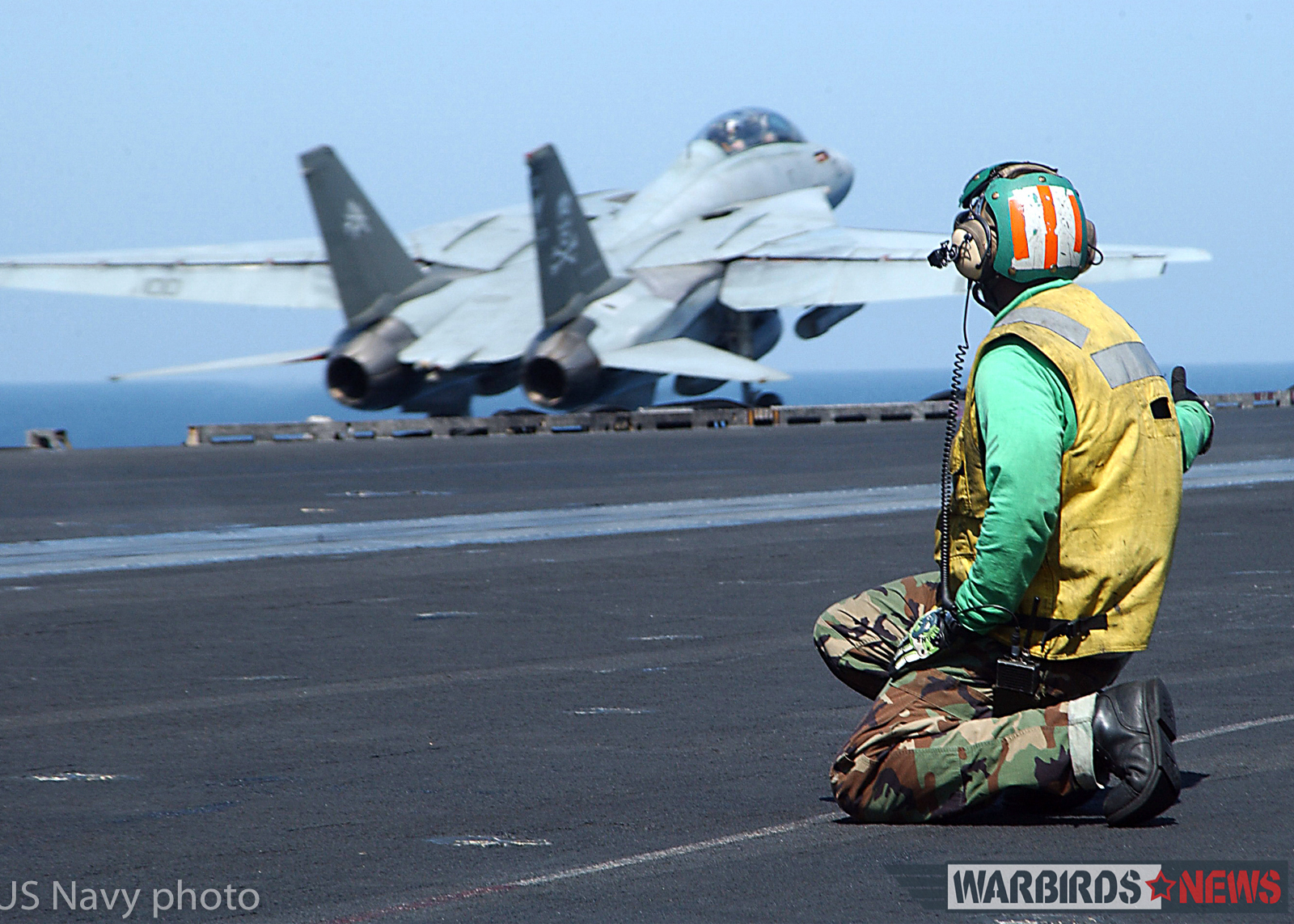 """At sea aboard USS George Washington (CVN 73) Sep. 8, 2002 -- Aviation Boatswain's Mate 2nd Class Michael Keys from Orlando, Fla., watches an F-14 """"Tomcat,"""" assigned to the """"Jolly Rogers"""" of Fighter Squadron One Zero Three (VF-103) gain altitude after launch. Washington is homeported in Norfolk, Va., and is on a six-month deployment conducting combat missions in support of Operation Southern Watch. U.S. Navy photo by Photographer's Mate Airman Jessica Davis. (RELEASED)"""
