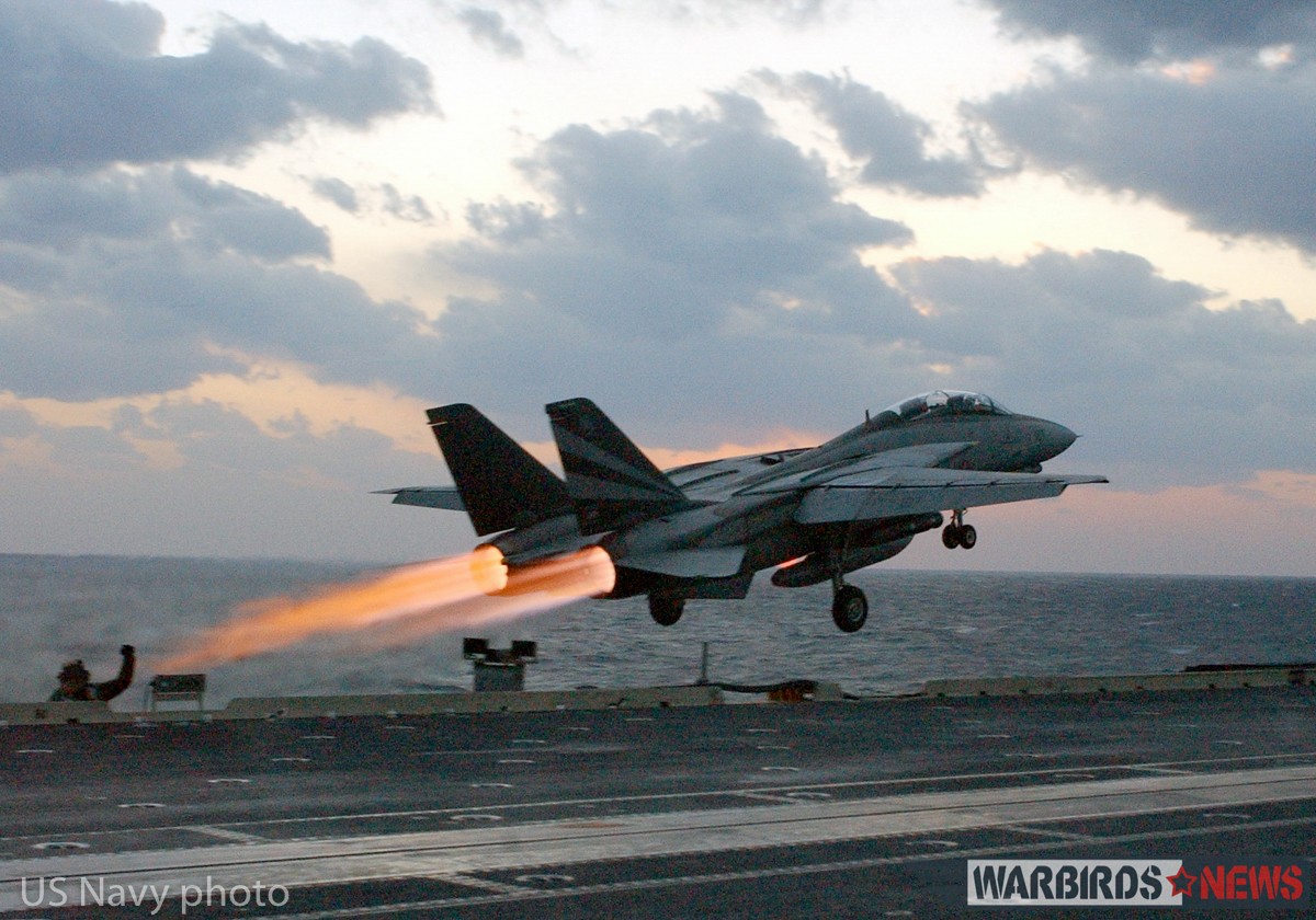 "At sea aboard USS Kitty Hawk (CV 63) Nov. 14, 2002 -- An F-14 ""Tomcat"" assigned to the ""Black Knights"" of Fighter Squadron One Five Four (VF-154) launches past steaming catapults on the bow of the ship. After an aircraft launches, steam is released as catapult pressure subsides. Kitty Hawk is the Navy's only permanently forward-deployed aircraft carrier and operates out of Yokosuka, Japan. U.S. Navy photo by Photographer's Mate 3rd Class Todd Frantom. (RELEASED)"