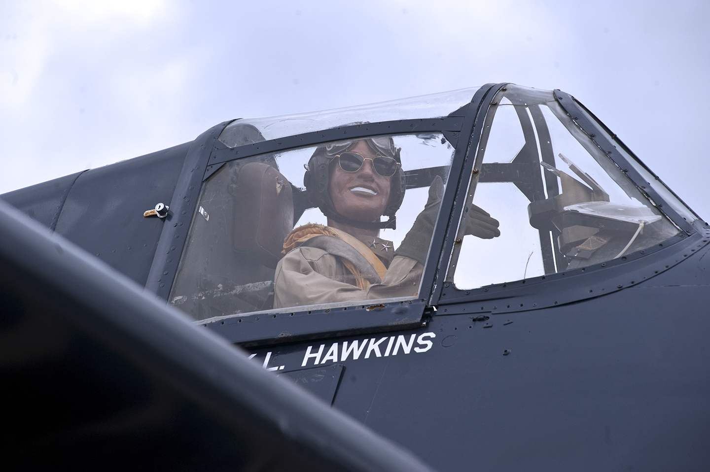 A close up of the Joint Base Andrews F6F-5K. The cockpit houses an animatronic manikin that salutes as cars drive by. It is wearing authentic navy dress donated by a veteran flyer from the USS Arizona. (photo via US Navy)