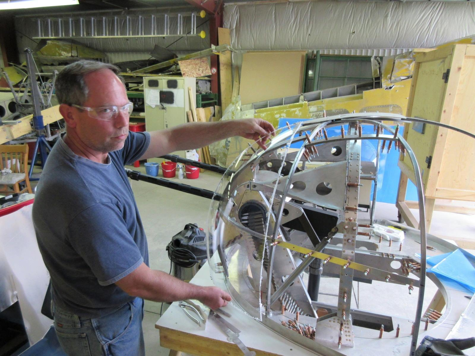 Dave Saulnier test-fitting a freshly formed Plexiglas panel to the replica nose turret. (photo by Malcolm Uhlman)