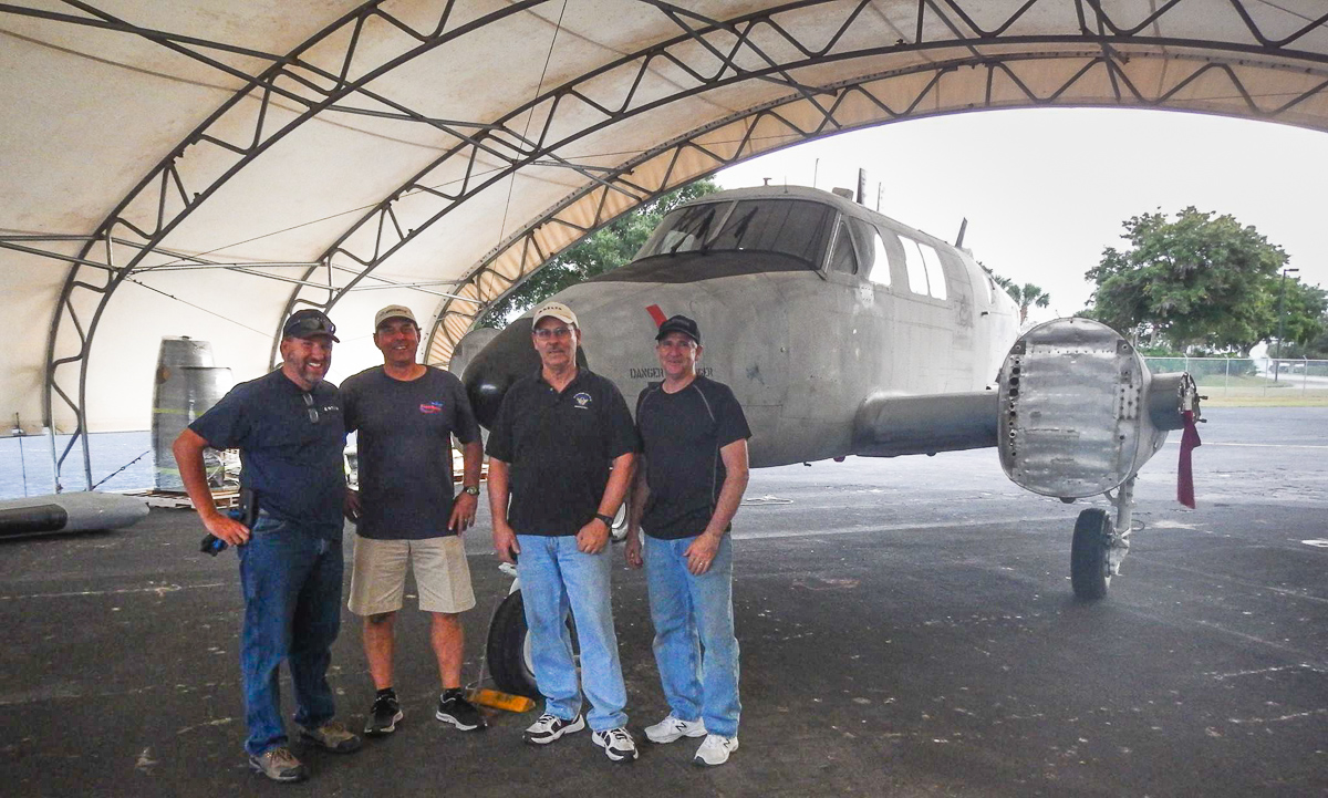 A group of Delta Airlines mechanics standing in front of the Ute in its temporary home at Orlando Executive Airport. These men will be part of the team  volunteering their time to rebuild the Ute for the 138th Aviation Company Memorial. (photo via Andrew Rodriguez)