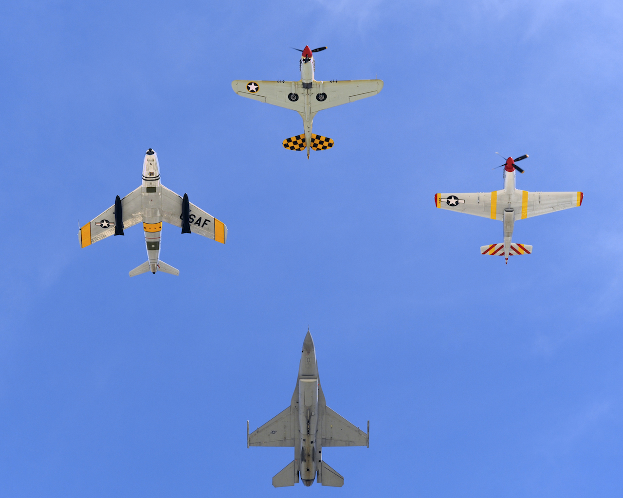 A U.S. Air Force F-16 Fighting Falcon (bottom) joins in formation with a P-40 Warhawk (top), P-51 Mustang (right), and a F-86 Sabre Jet (left) over Davis-Monthan Air Force Base, Ariz., during Heritage Flight Training Course March 2, 2014. During the course aircrews practiced ground and flight training to allow civilian pilots of historic military aircraft and current Air Force fighter pilots to safely fly in formations together, in preparation for the upcoming Open House. (U.S. Air Force photo by Airman 1st Class Chris Massey/ Released)