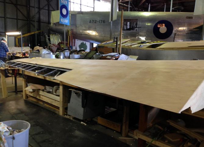 The left wing nearing completion. RAAF Liberator A72-176 can be seen in the background. (photo via B-24 Liberator Memorial Fund)