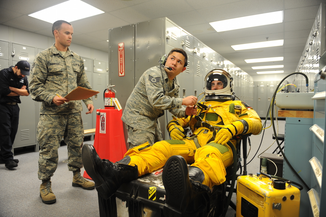 Staff Sgt. Timothy Dayrit (center), and Staff Sgt. Joseph Kennedy (left), 9th Physiological Support Squadron full-pressure suit technicians perform pre-flight full-pressure suit maintenance for Capt. Travis, 99th Reconnaissance Squadron U-2 pilot, Sep. 19, 2015, at Joint Base Andrews, Maryland. The full-pressure is worn by U-2 Dragon Lady pilots who frequently fly at the edge of space. (U.S. Air Force photo by Senior Airman Bobby Cummings/Released)