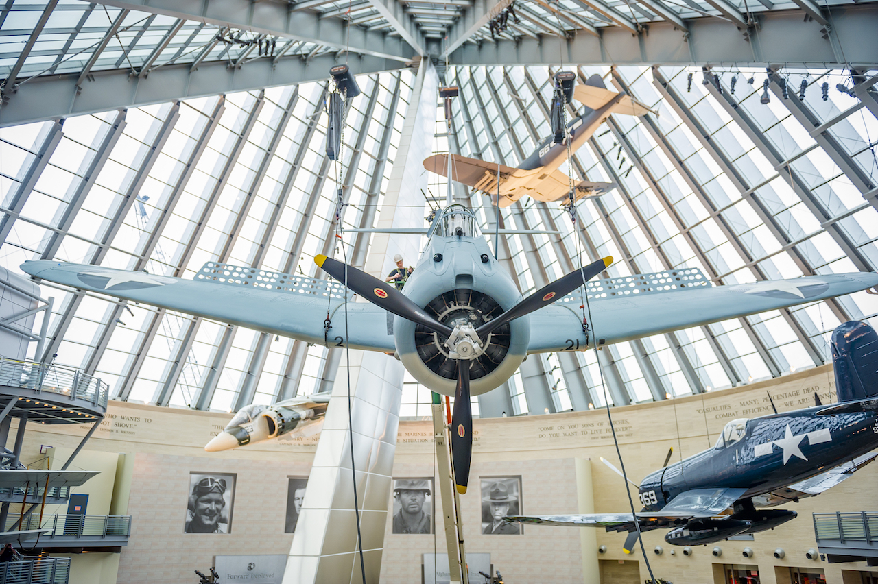 An SBD-3 (Scout Bomber Douglas) Dauntless, is weight tested, lifted and installed as part of the World War II exhibit at the National Museum of the Marine Corps, Triangle, Va., Feb. 9, 2016. This fully restored, donated aircraft has been painted to represent the SBD-3 flown by Maj. Richard C. Mangram and Cpl. Dennis E. Byrd during the Guadalcanal Campaign on Aug. 25, 1942. (Official United States Marine Corps photo by Kathy Reesey/Released)