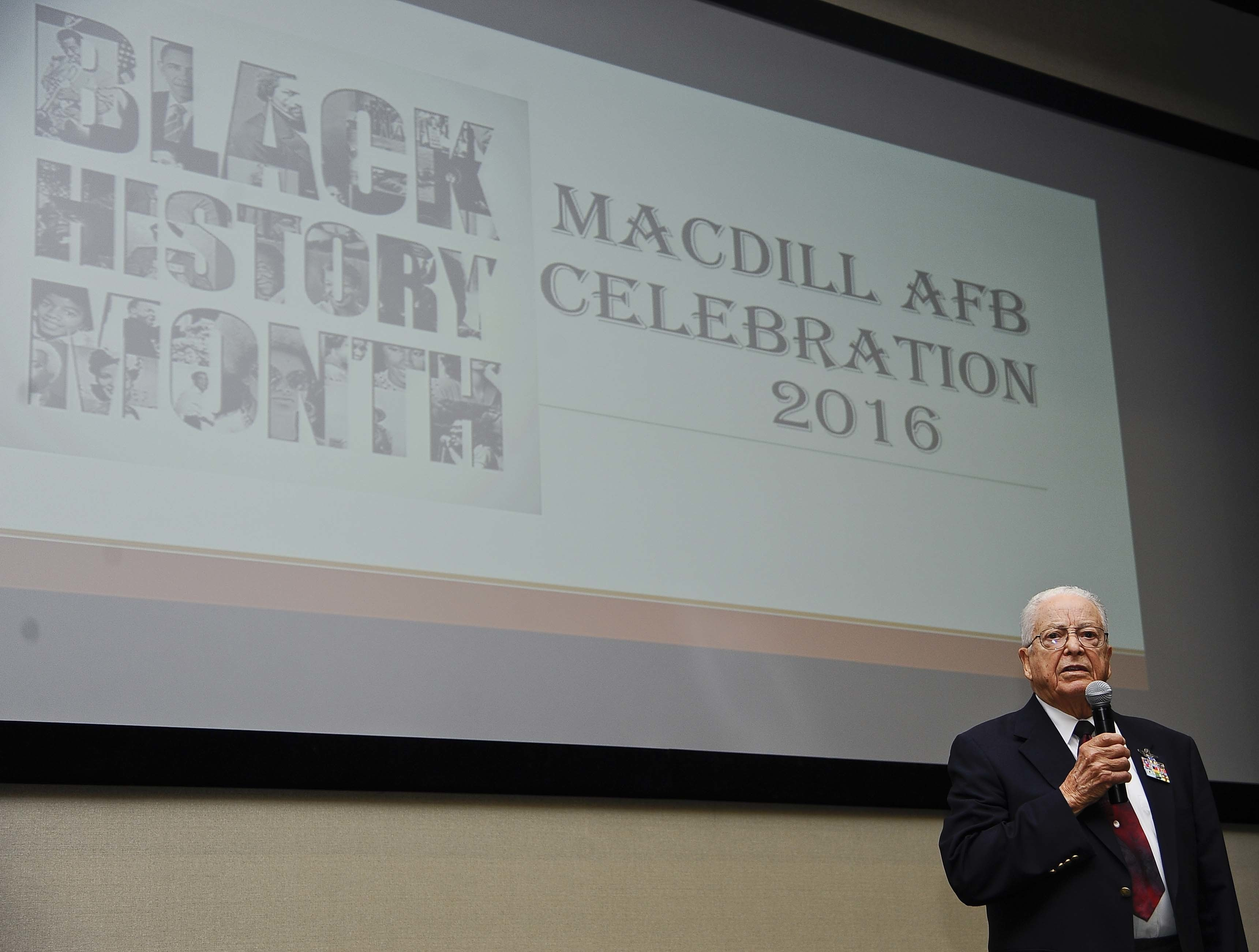 """Retired Lt. Col. George E. Hardy, a Tuskegee Airman, gives a speech during the """"A Salute To A Living Legend"""" event at MacDill Air Force Base, Fla., Feb. 11, 2016. In September of 1944, he was assigned to the famous 99th Fighter Squadron, 332nd Fighter Group at Ramitelli Air Base, Italy, where he would participate in 21 escort and strafing missions over Europe. (Photo by SrA Vernon Fowler)"""