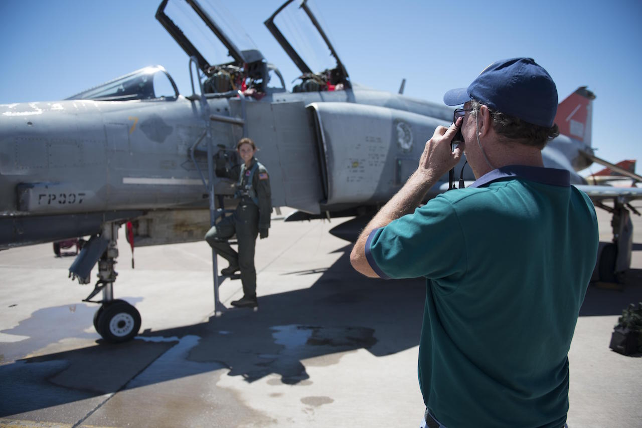 Retired Col. David takes a photo of his daughter, Cadet 2nd Class Kaitlyn, standing next to an F-4 Phantom on July 12, 2016 at Holloman Air Force Base, N.M. David came to surprise his daughter, a junior at the Air Force Academy, after her first flight in a fighter jet with the 82nd Aerial Target Squadron. (Last names are being withheld due to operational requirements.
