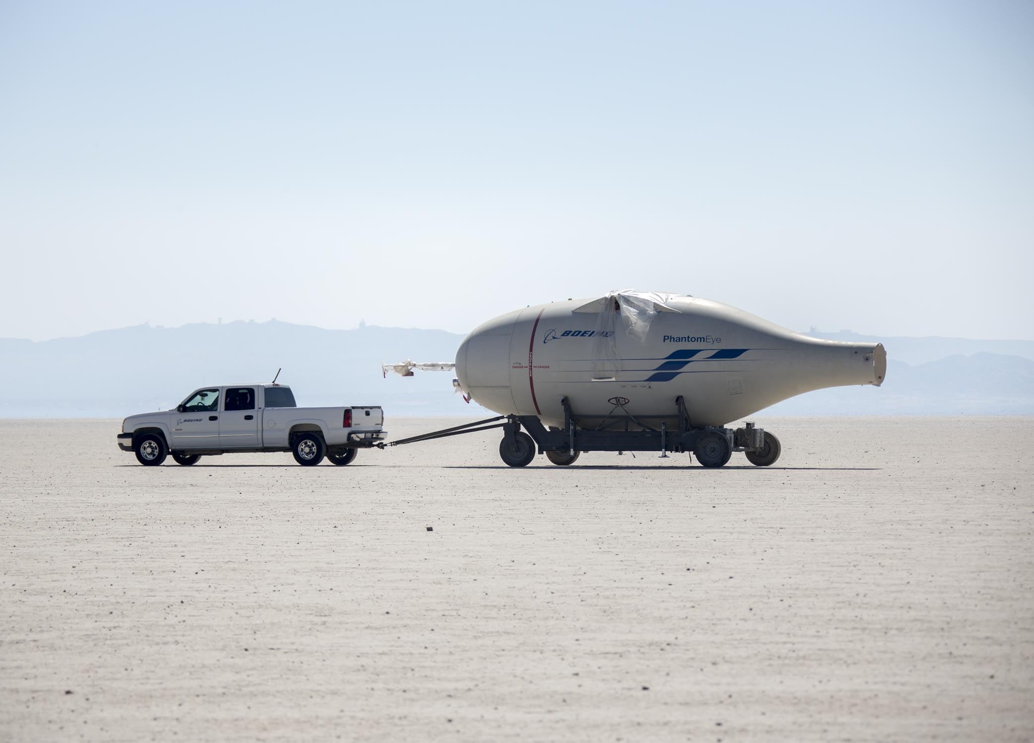 EDWARDS AIR FORCE BASE, Calif. (Aug. 17, 2016) Photos of NASA employees moving the disassembled Phantom Eye, a Boeing-developed, liquid hydrogen-powered demonstrator aircraft, during a transfer from the NASA Armstrong Flight Research Center across Rogers Dry Lake to the red-topped Hanger 4305 on North Base, where the aircraft will await reassembly and refurbishment for eventual display as part of the Air Force Flight Test Museum. Phantom Eye was designed to fly long endurance missions at high altitudes as a potential surrogate for military intelligence and communications satellites. Smoke from the Blue Cut Fire can be seen in the background of some images. (U.S. Air Force photo by Christopher Okula)