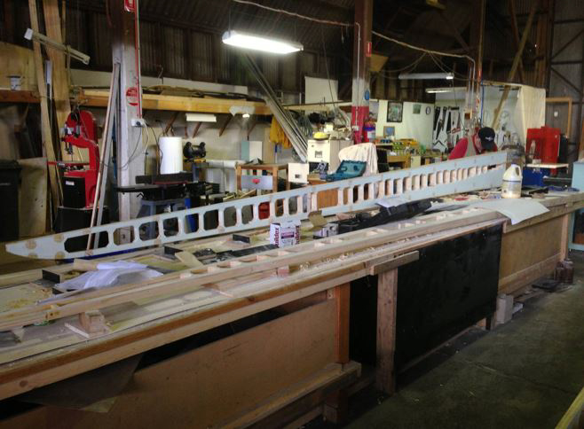 A wing main spar takes shape on the work bench. (photo via B-24 Liberator Memorial Fund)