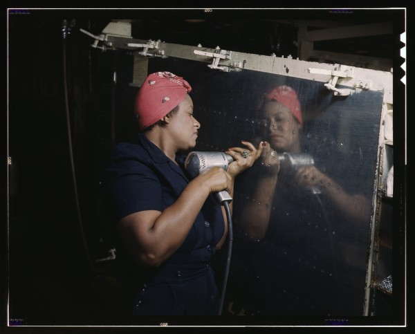 "One of the many thousand ""Rosie the Riveters"" at work  in a WWII aircraft factory."