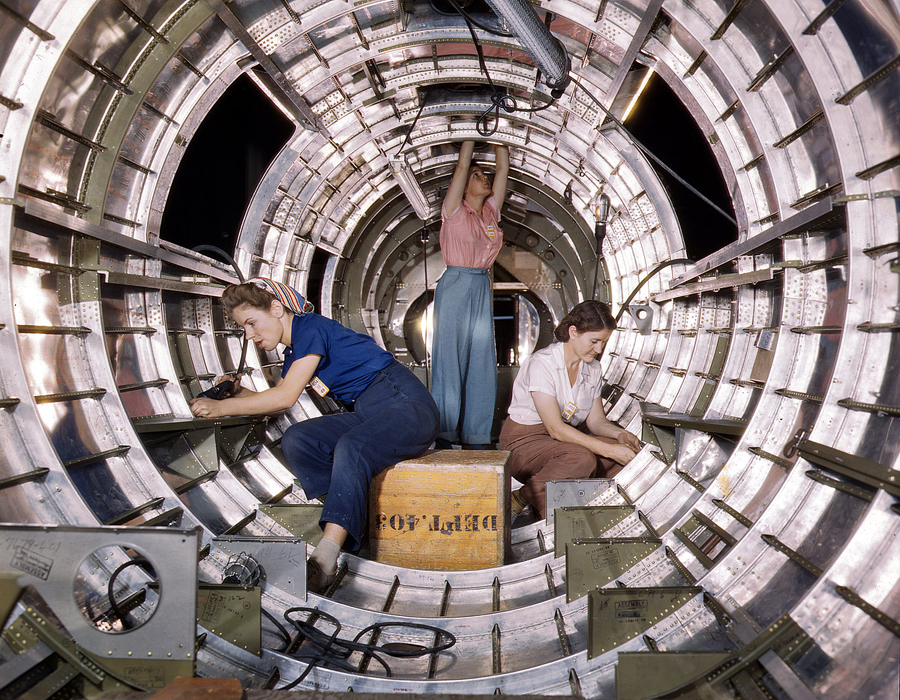 Workers installing fixtures and assemblies in the tail section of a B-17F bomber.