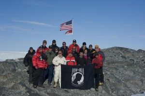 An expedition team of U.S. Coast Guard service members and North South Polar, Inc. scientists and explorers display the POW/MIA flag in honor of the expedition to find the crash site of a WWII Coast Guard Grumman Duck. (Photo credit: USCG)
