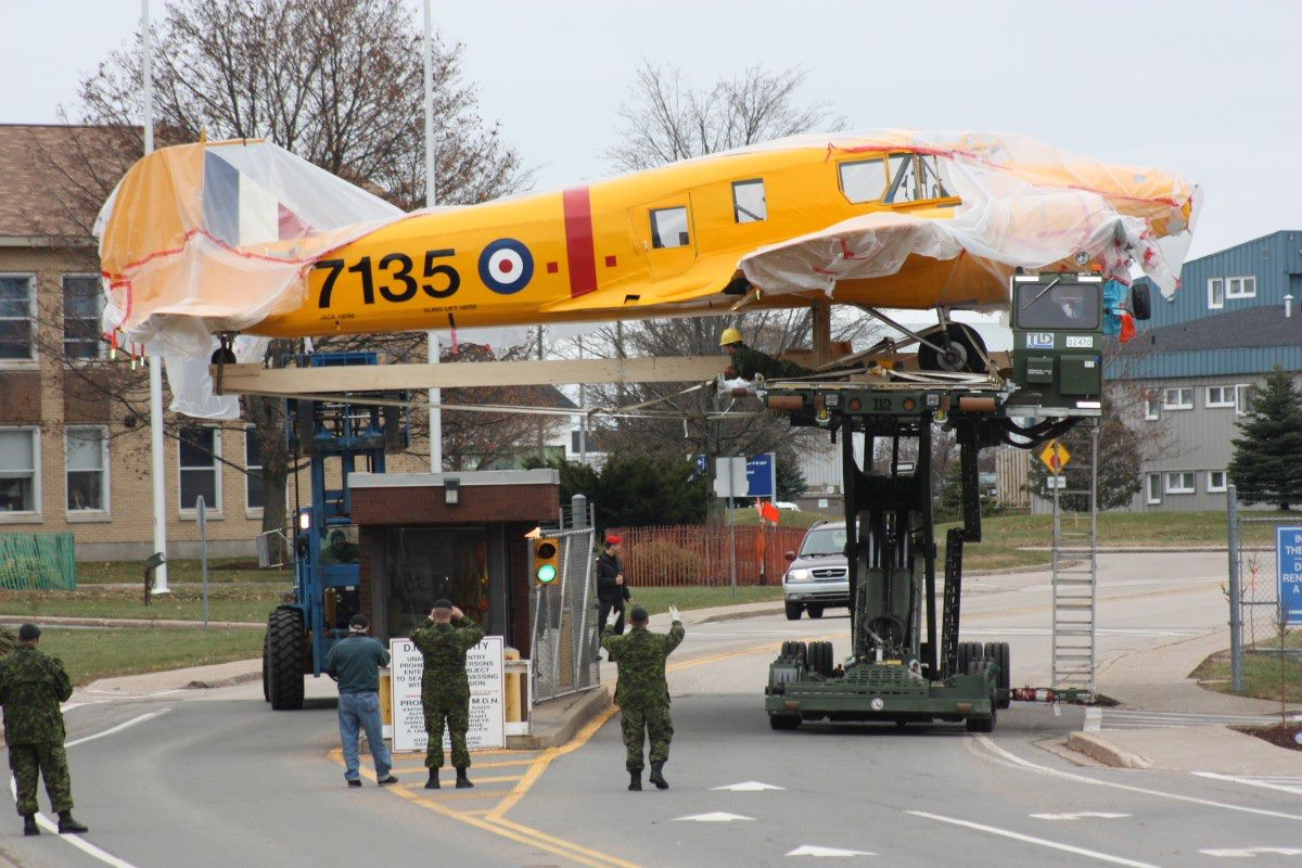 A pair of heavy duty forklifts maneuver the prize winning Anson over the base's guard station enroute to its new home. (Photo credit: Greenwood Military Aviation Museum)