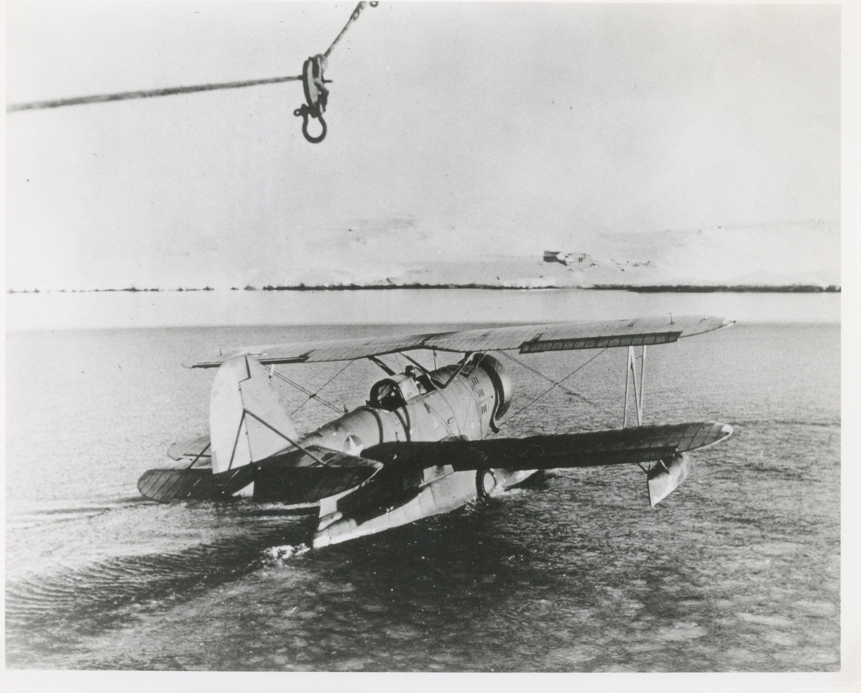 "Original caption: ""THE TAKE OFF: The Coast Guard amphibian plane (J2F) has been put over the side, and Lieutenant John A. Pritchard, Jr. and Radioman Benjamin A. Bottoms, ready for the take-off, scan the Greenland icebergs over which they have spent so many hours of hazardous flying in their single-engine plane.  They successfully rescued two of the U.S. Army fliers and met their death in an attempt to rescue the [sic] third flier."" (photo credit: USCG Archives)"