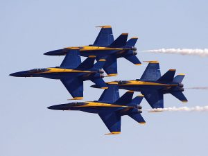 The Blue Angels F/A-18 Hornets fly in their signature tight diamond formation, maintaining a hair-raising 18-inch wing tip to canopy separation.