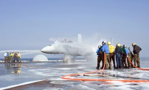 Crash and salvage teams spray an aircraft during a training exercise aboard the aircraft carrier USS George Washington (CVN 73) (Image Credit: US Navy)