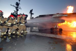 A repair locker hose team aboard USS John F. Kennedy (CV 67) combats a controlled fire on the MAFTD.  (Image Credit: US Navy)