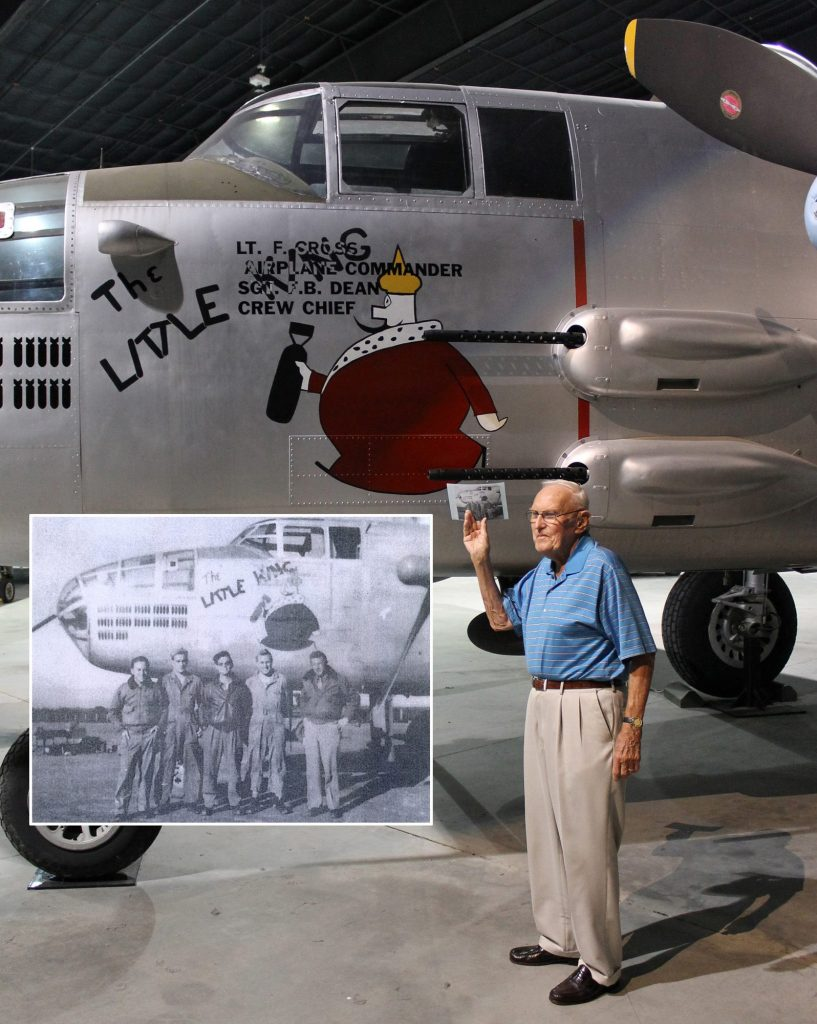 "Tail Gunner Norris holds a copy of a photo that shows his crew standing by the original ""The Little King."" In that photo (see inset), Norris is the second from the right. (Image Credit: Museum of Aviation)"