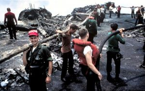 Crewmen battle the remnants of the blaze that literally burned the F-4B Phantoms in the background to the ground (Image Credit: US Navy)