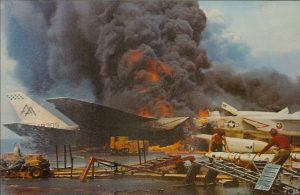 Fire aboard the US Navy aircraft carrier USS Forrestal (CVA-59) on July 29, 1967. Two North American RA-5C Vigilantes  burn on the starboard side aft of the island, while crewmen remove AGM-45 Shrike missiles in the foreground. (Image Credit: US Navy)