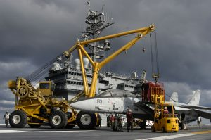 Crash-and-salvage personnel rig a training skeleton of an F-14 Tomcat to a mobile crane used to move damaged aircraft off the flight line during crash and salvage operations aboard the USS Kitty Hawk (CV 63) (Image Credit: US Navy)