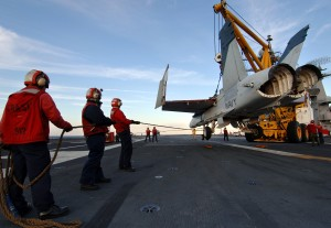 Crash and salvage personnel keep an F/A-18 Hornet training airframe steady as it is lifted from the landing area during a simulated crash landing aboard the USS Harry S. Truman (CVN 75) (Image Credit: US Navy)