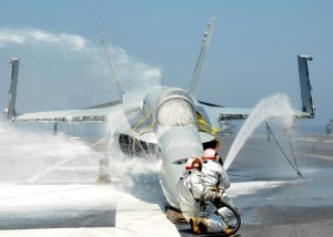 Sailors assigned to the crash and salvage crew on  USS George H.W. Bush (CVN 77) spray foam on an F/A-18 Hornet training aircraft during a firefighting drill. (Image Credit: US Navy)