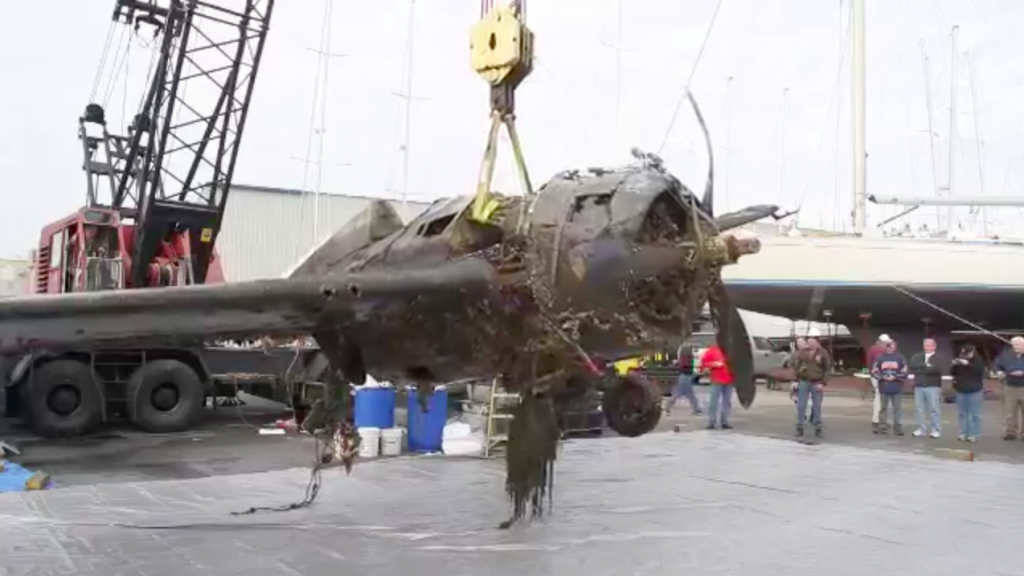 Wildcat FM-2 57039, Lifted from the water, heading to Air Zoo for a full restoration