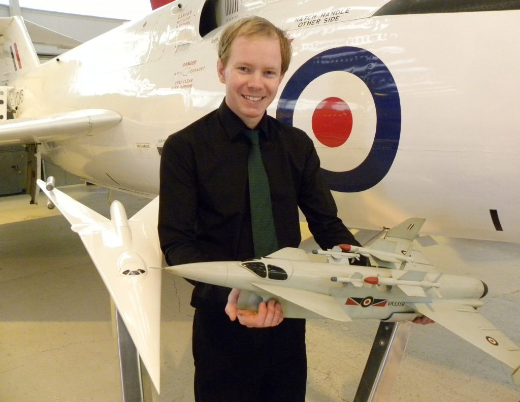 RAFM Curator Nick Sturgess with two concept models, holding the Vickers Type 559. (Image Credit: RAF Museum)