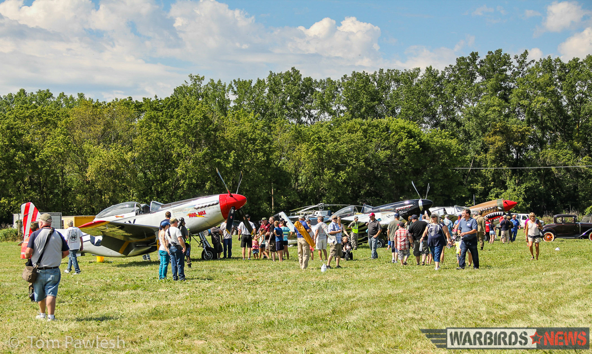 The crowd getting an up-close look at some of the warbirds on display. Nothing beats a grass airfield for showing off WWII aircraft! (Photo by Tom Pawlesh)