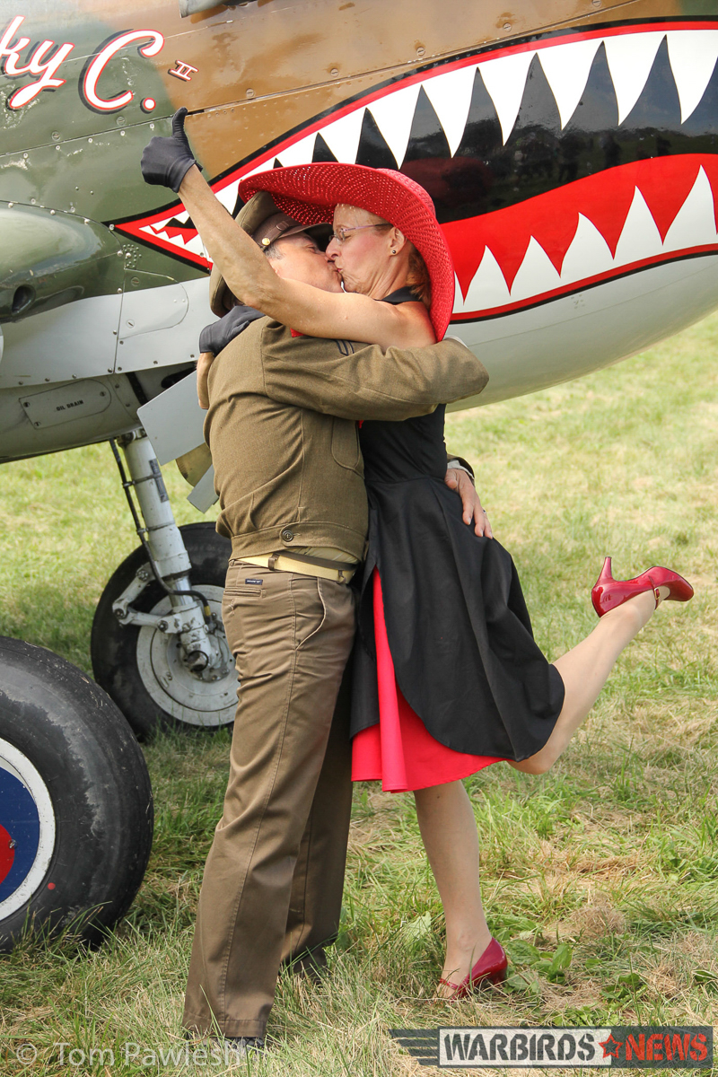 A pair of WWII re-enactors share a bit of romance in front of the Warhawk... and why not indeed? (Photo by Tom Pawlesh)