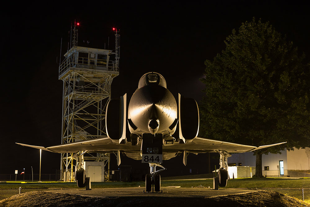 A dramatic night shot of F-4C Phantom II 64-0844 on display outside the museum. In the background is the old basm tower still in use today with the now-civilian airport. (photo by Gary Scroggins via Atterbury-Bakalar Air Museum)