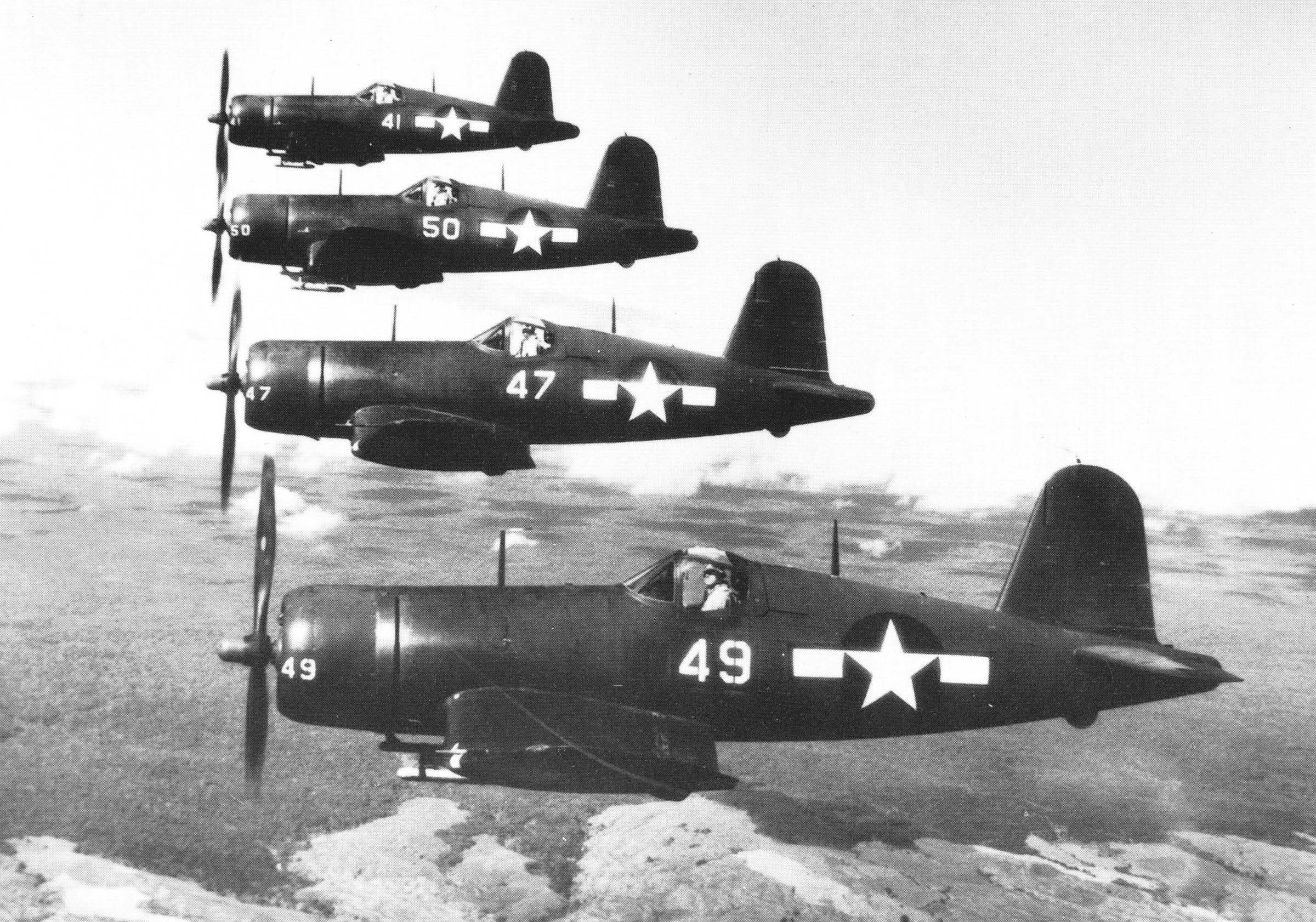 A four-ship line abreast formation of Chance-Vought F4U Corsairs over the Hawaiian Islands during WWII. [Photo Credit: National Archives]