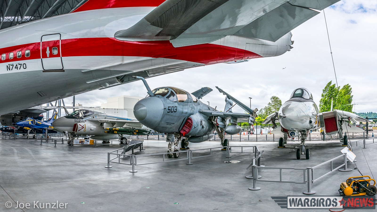 Four Cold War-era naval jets sit beneath the tail of the first 747. (photo by Joe Kunzler)