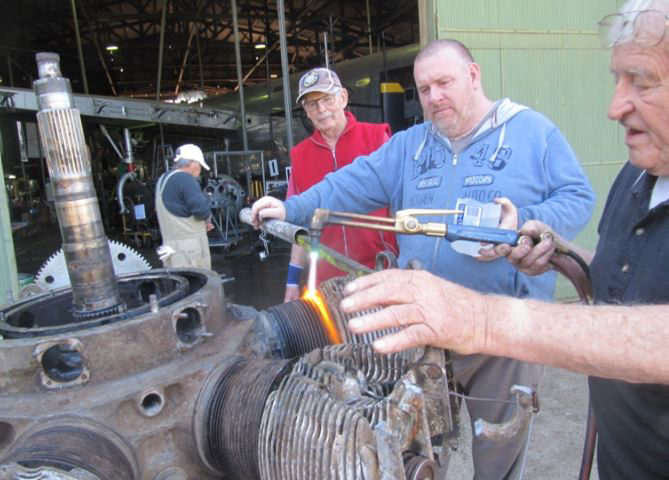 Volunteers working on one of the Oxford's engines. They are heating and cooling the cylinder barrel in an attempt to separate it from the engine core for servicing. (photo via B-24 Liberator Memorial Fund)