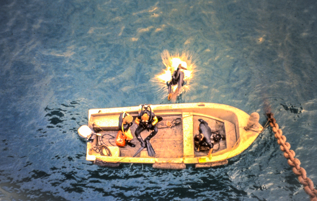 The Currituck's divers are going over the side of the ship to check if North Vietnamese divers had concealed mines under the ship overnight. (photo by Raymond T. West)