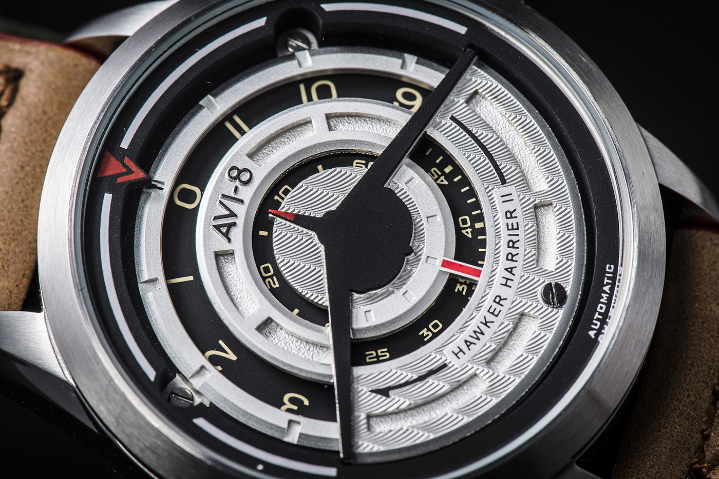 A close-up view of the watch dial clearly shows the Harrier silhouette in black on the front, and how it subtly indicates the time with the rotating discs displaying the hour, minute and second.