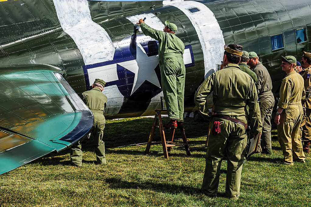 Re-enactors and veterans painting the D-Day stripes on the TFLM C-53 Skytrain at AirVenture 2013 in much the same way as it was done during WWII... with mops and paint brushes. (photo by Jake Peterson)