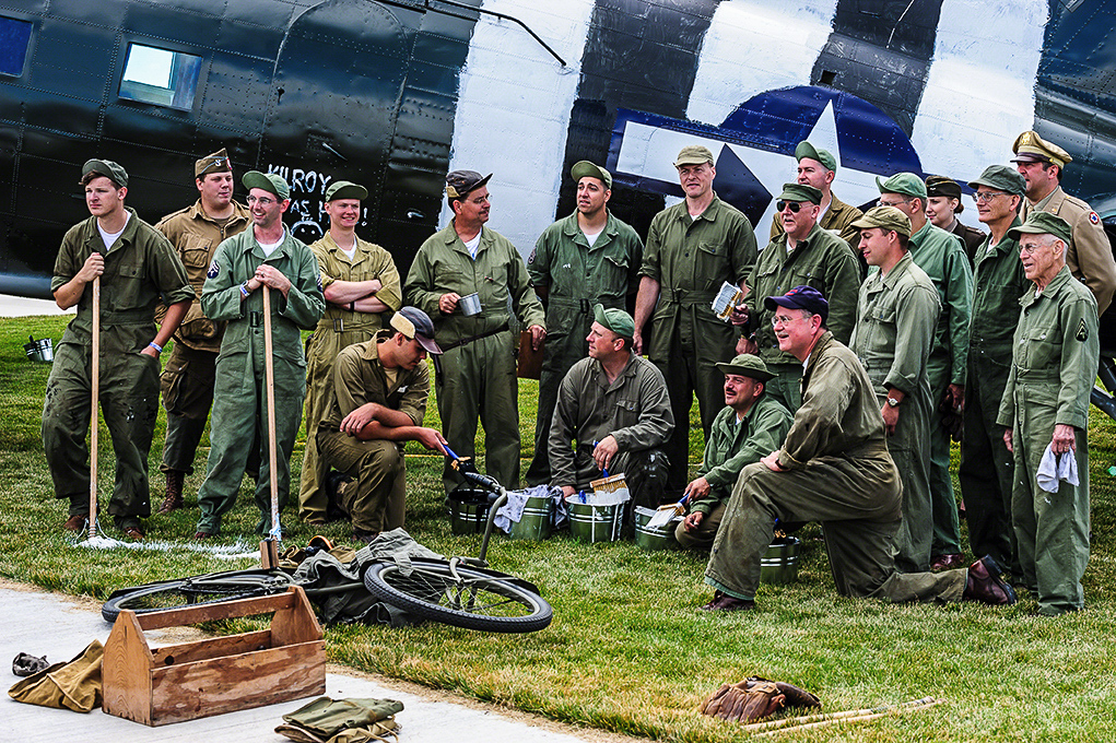 Re-enactors and veterans pose after painting the D-Day stripes on the TFLM C-53 Skytrain at AirVenture 2013. (photo by Jake Peterson)