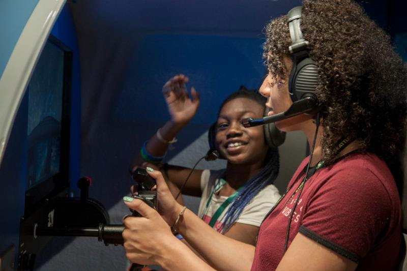 After learning aeronautics and aviation basics, plan a flight and perform preflight checkouts in a real airplane, these girls take their trip on a flight simulator in the Museum's Aviation Learning Center.
