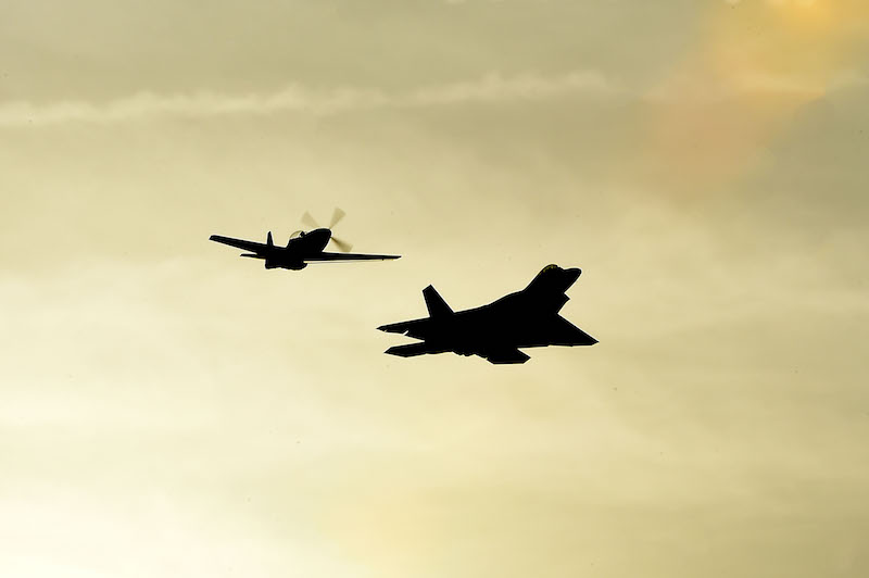 An F-22 Raptor and an P-51 Mustang perform a twilight show during the Wings Over Golden Isles Air Show in Brunswick, Ga., March 24, 2017. The duo performed a Heritage Flight, which is a performance of current fighter and attack aircraft flying with World War II, Korea and Vietnam era fighter aircraft. (U.S. Air Force photo/Senior Airman Kimberly Nagle)