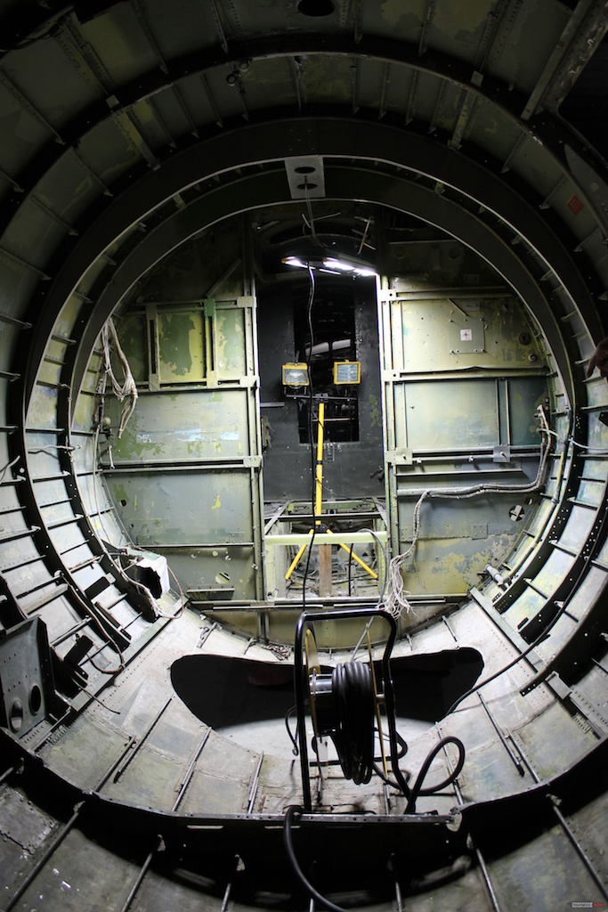 Inside the waist section looking forward. The yellow light stand is in the radio room. The fuselage is designed to be separated at a production break just behind the wall or bulkhead separating the radio room from the waist compartment. The hole in the floor is where the ball turret was located. ( Photo via Museum of Aviation Warner Robins AFB)