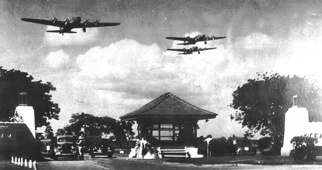 Boeing B-17D Fortresses of the 5th Bombardment Group overfly the main gate at Hickam Field, Hawaii Territory during the summer of 1941. 21 B-17C/Ds had been flown out to Hawaii during May to reinforce the defenses of the islands. (Photo via Wikipedia)