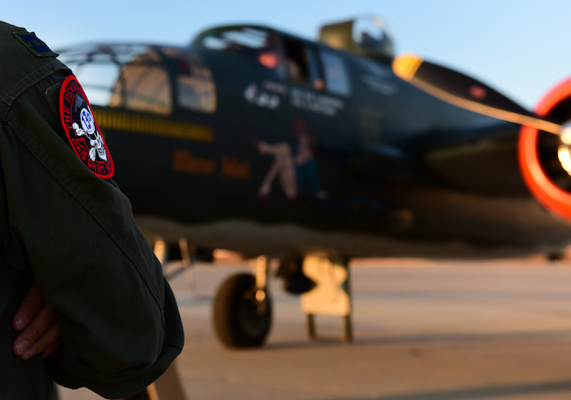 A B-2 Spirit Bomber pilot, from the 13th Bob Squadron (BS) stands in front of a North American B-25 Mitchell at Whiteman Air Force Base, Mo., June 11, 2017. The 13th BS has participated in every war since World War I and celebrated 100 years of service on June 14, 2017. (U.S. Air Force photo by Tech. Sgt. Tyler Alexander)