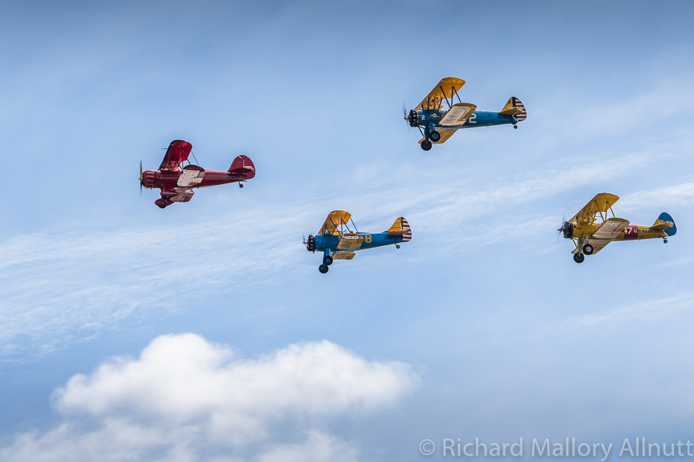 Two WACOs and two Stearman biplanes from the Bealeton Flying Circus fly by in formation. Based nearby in Bealeton, the Flying Circus thrills the crowds every Sunday from May to the end of October each year since the early 1970s. (photo by Richard Mallory Allnutt)