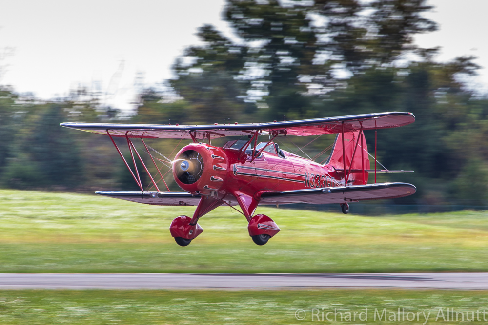 John Corradi lands his magnificent scarlet WACO YMF reproduction following his display routine. A Viet Nam veteran, Corradi is one of the stalwarts of the Bealeton Flying Circus, located just down the road from Culpeper in Bealeton, Virginia. (photo by Richard Mallory Allnutt)