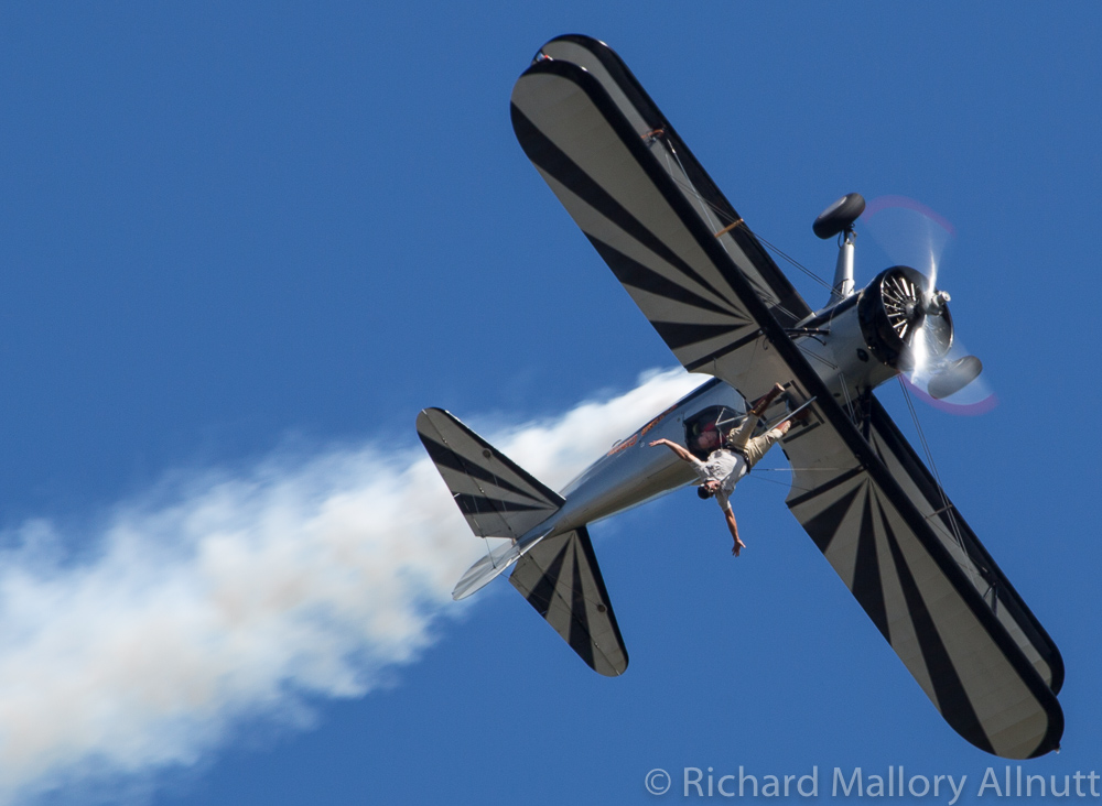 Wing walker Chuck Tippett holding on to his post by just the toes of his right foot as Kirk Wicker puts the Stearman into a roll. (photo by Richard Mallory Allnutt)